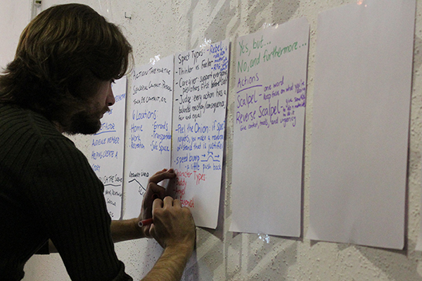 Shea writing on wall post-its during interactive training session